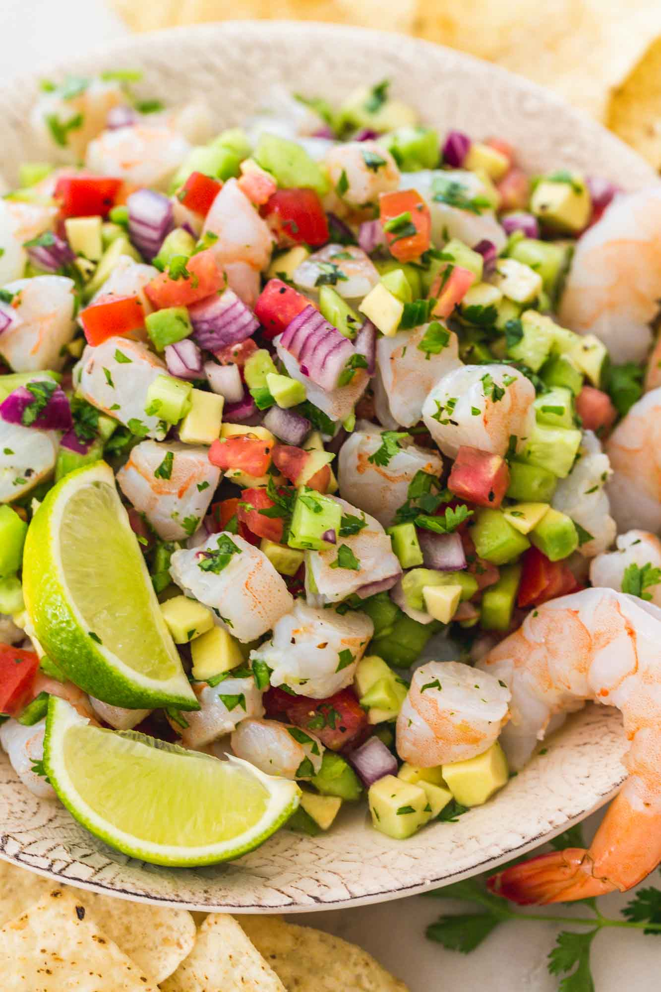 Shrimp ceviche served in a bowl with fresh lime wedges and poached shrimp