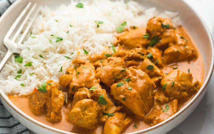 Butter chicken served with rice in a white bowl, garnished with chopped parsley.
