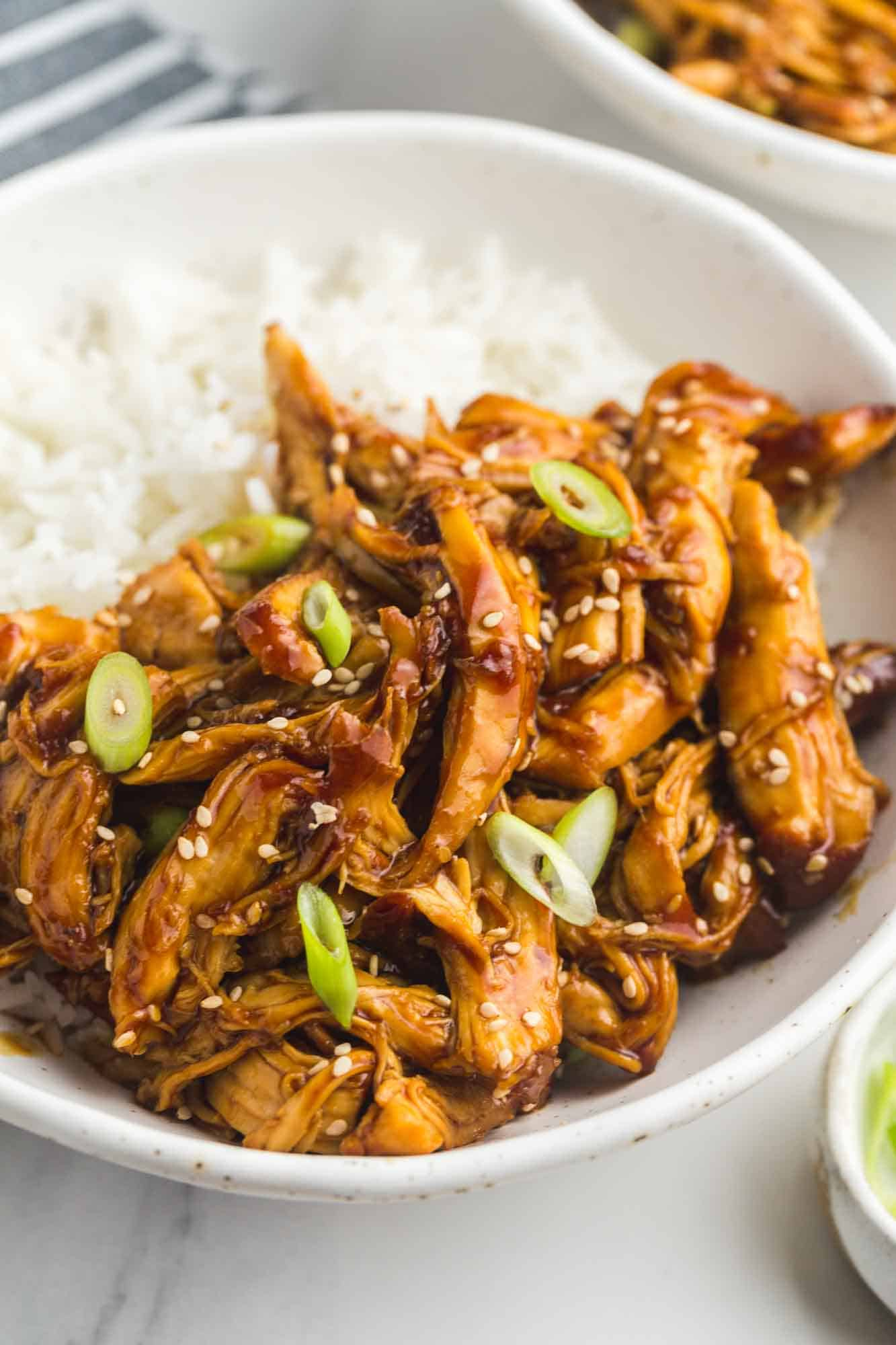 Slow Cooker Teriyaki Chicken served in a white bowl over rice, with toasted sesame seeds and sliced scallions