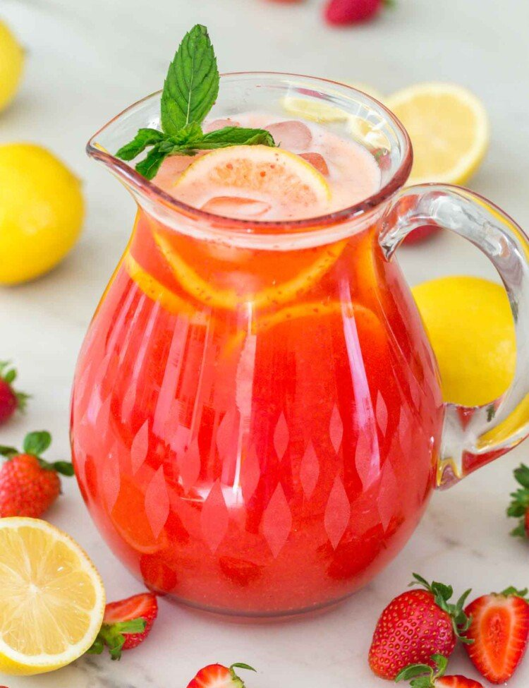 Strawberry lemonade in a glass pitcher with fresh strawberries and fresh lemons