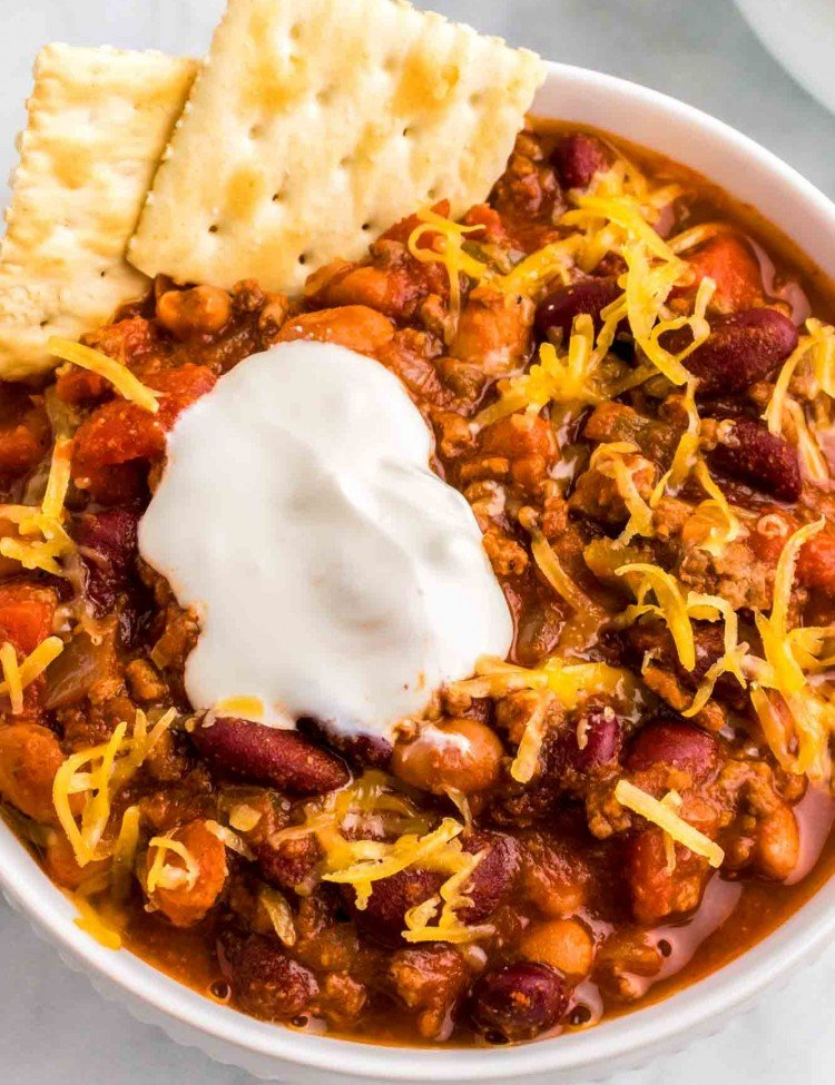 Wendy's Chili served in a white bowl with saltines, sour cream and shredded cheese.