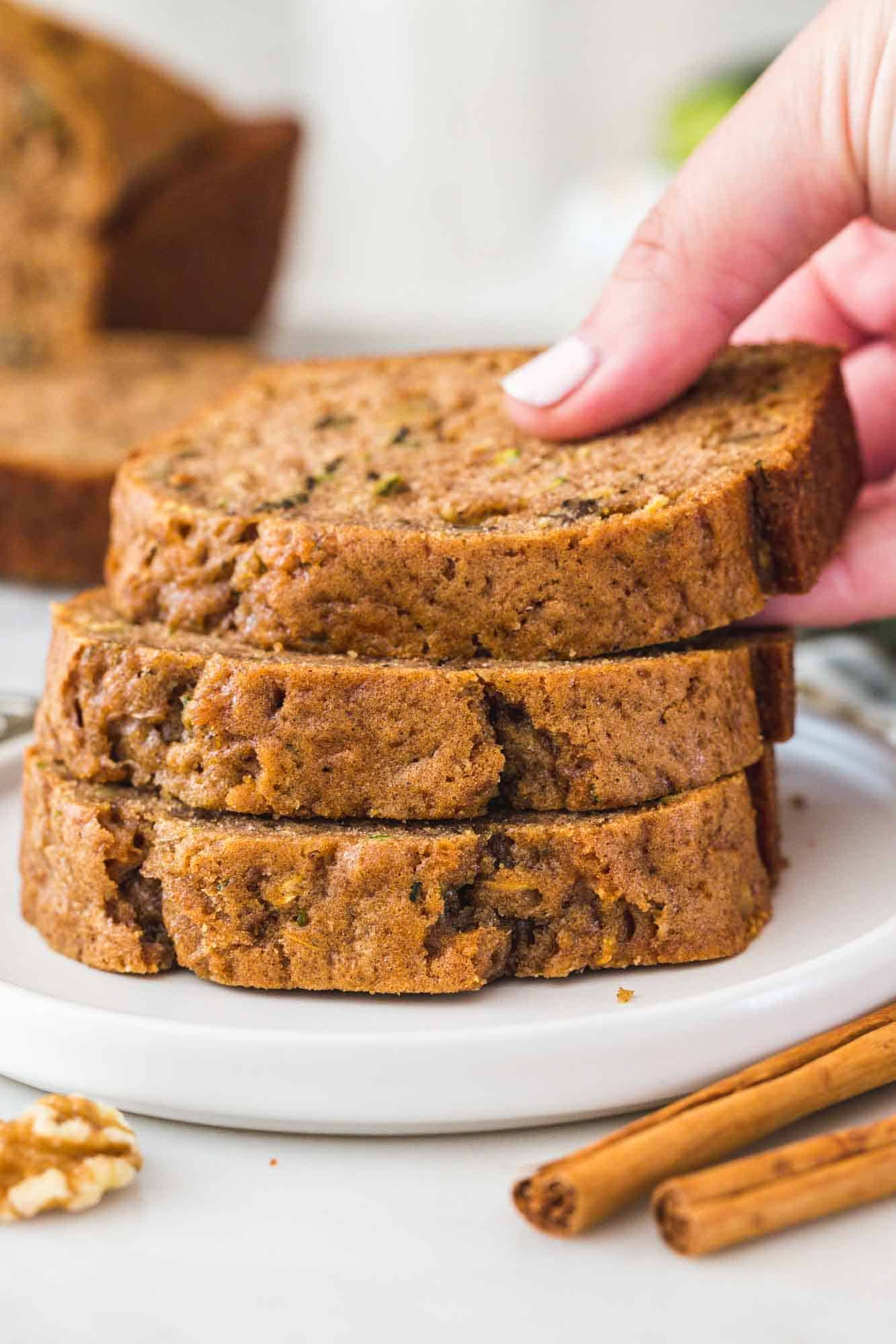 Stacked zucchini bread slices and a hand