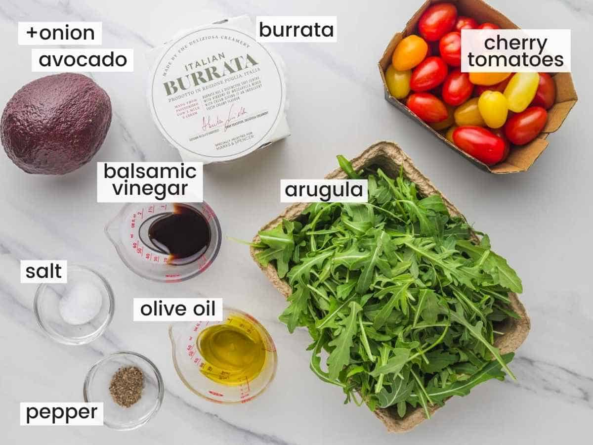 Ingredients needed to make burrata salad including cherry tomatoes, arugula, avocado, burrata cheese ball, and dressing ingredients.