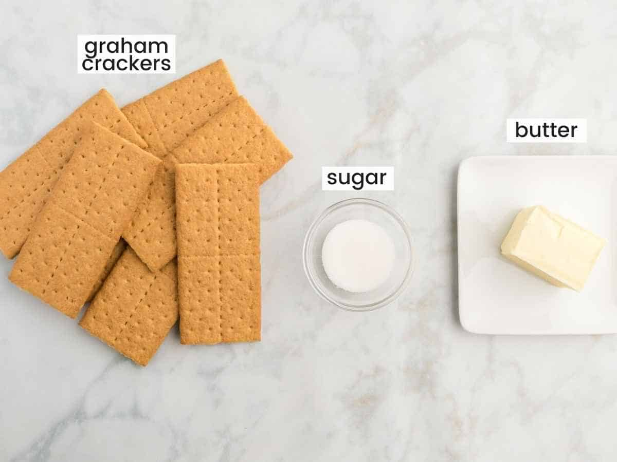 Ingredients needed to make a cheesecake crust including graham crackers, sugar, and butter.