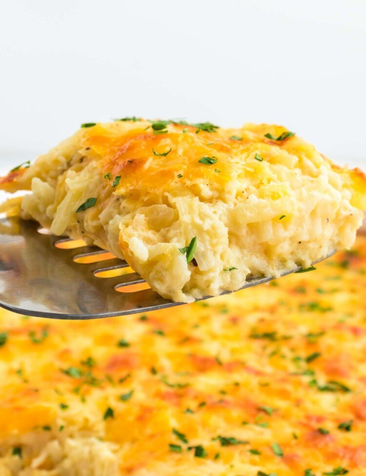 A slice of cheesy casserole being served from the casserole dish