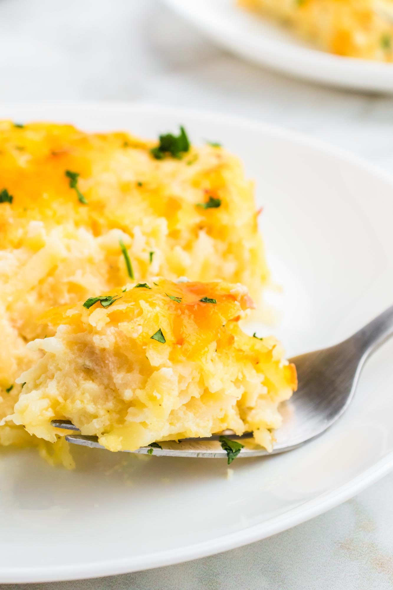Taking a bite of Cracker Barrel hashbrown casserole with a fork