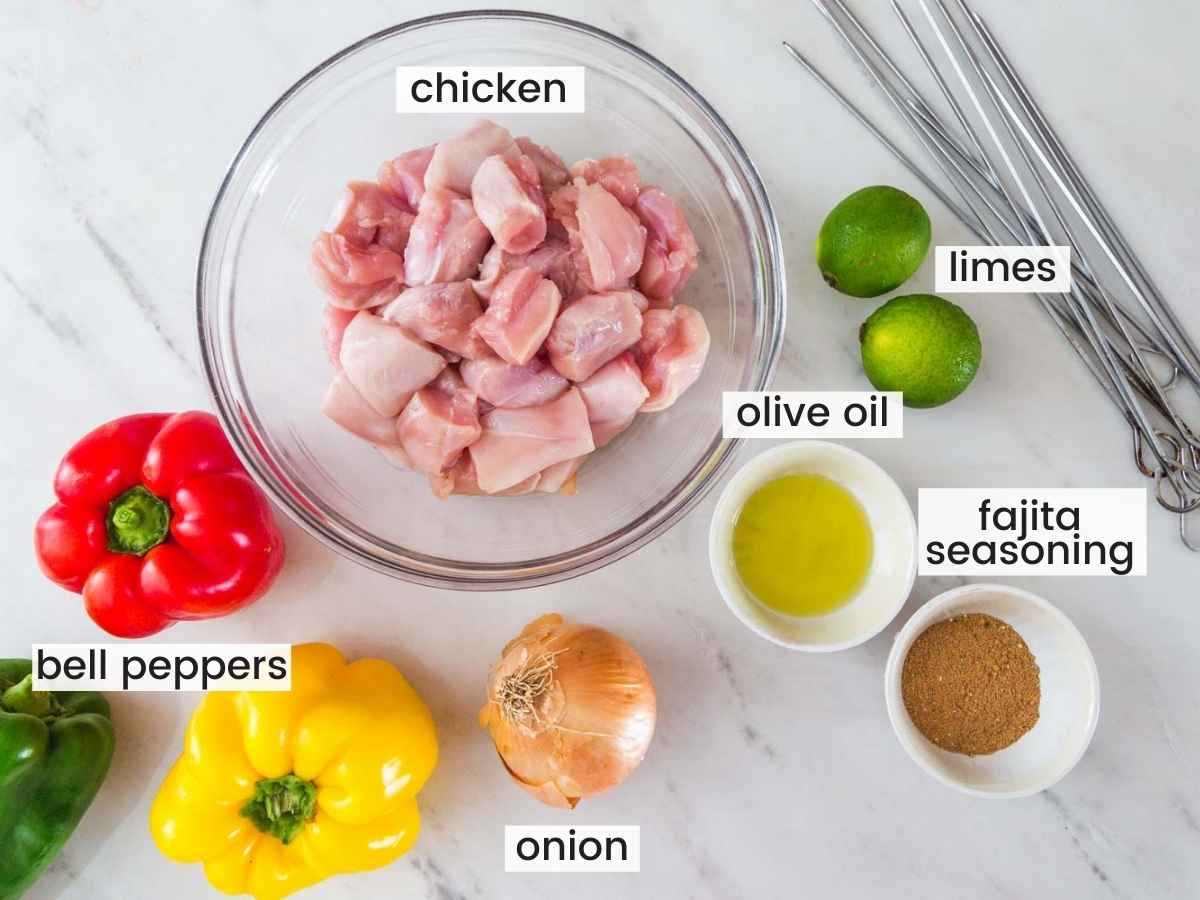 Ingredients needed to make fajita chicken kabobs including chicken, bell peppers, onion, seasoning, lime, and olive oil.