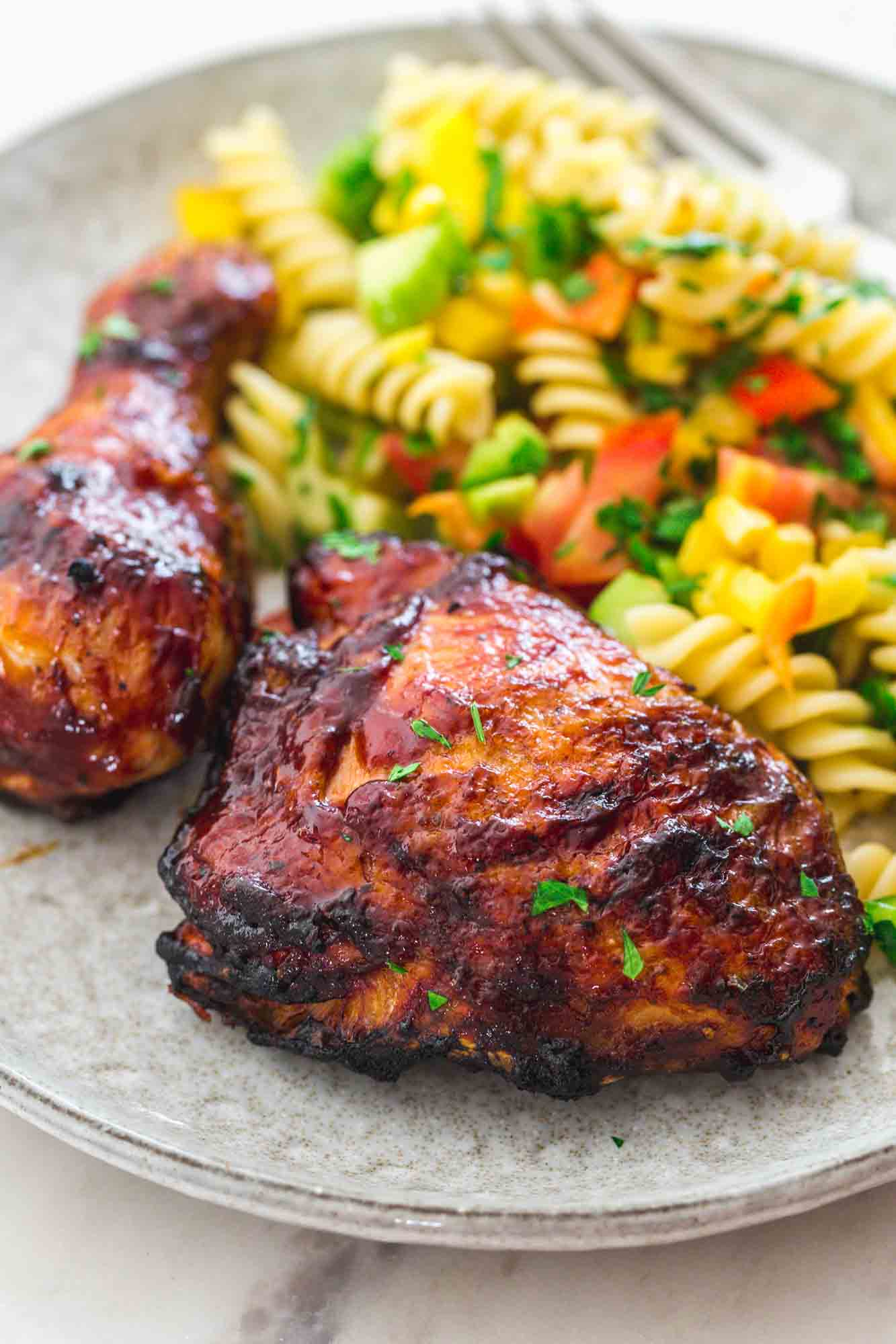 Grilled BBQ Chicken thigh and drumstick served in a plate with pasta salad