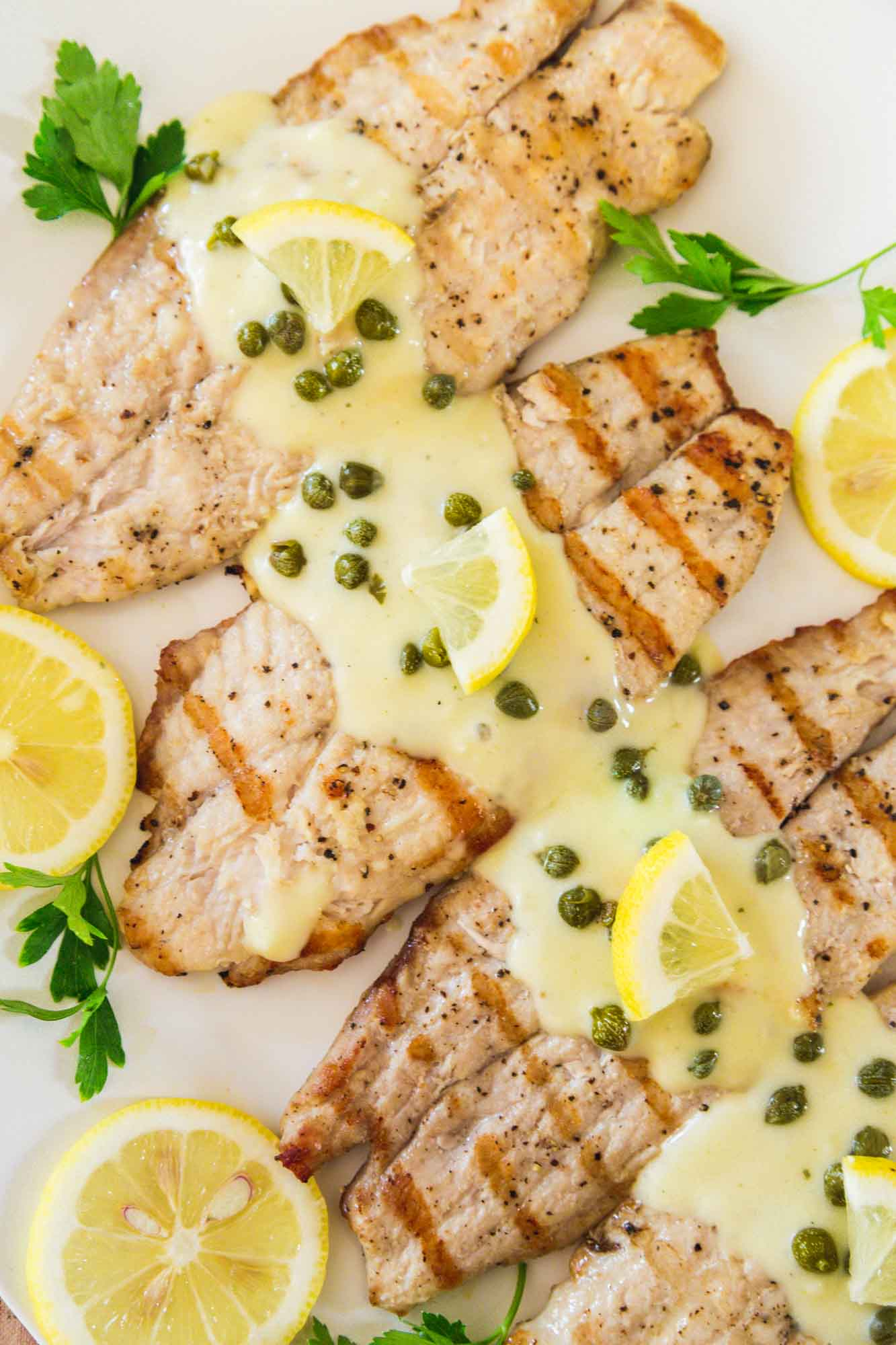 Overhead shot of grilled tilapia on a white platter with piccata sauce and capers