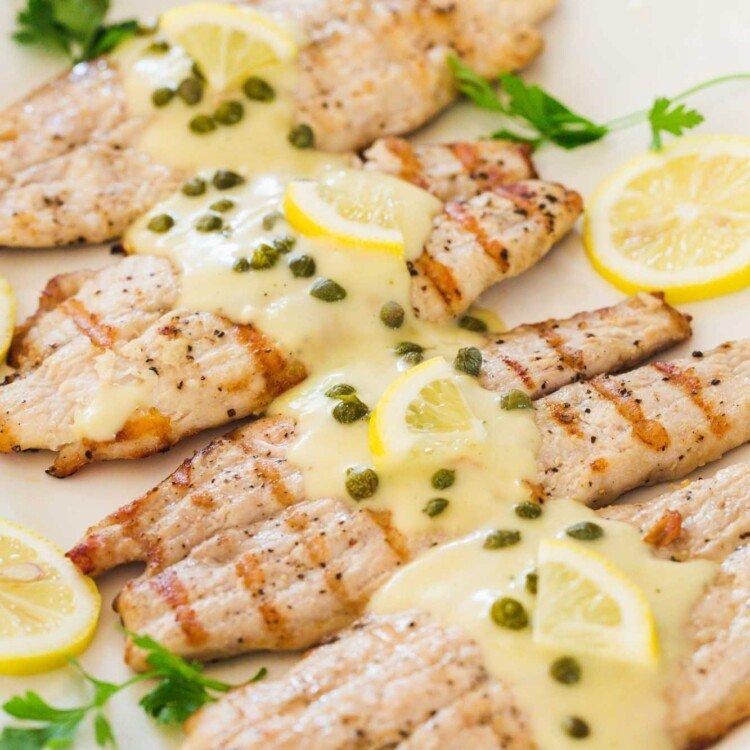 Grilled tilapia served on a platter, and topped with piccata sauce, capers and fresh lemon slices.