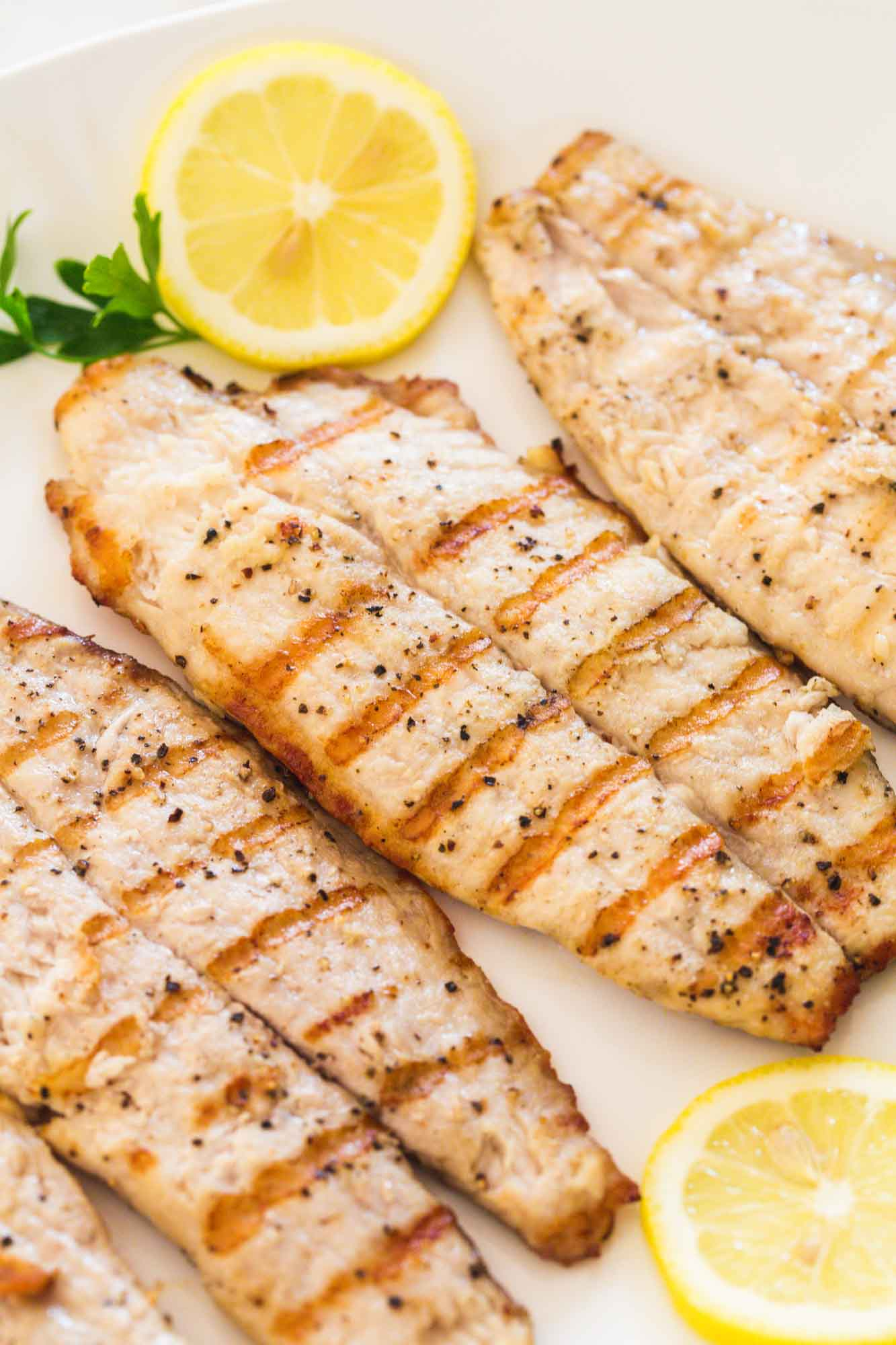 Grilled tilapia fillets served on a large white platter with fresh lemon slices and parsley