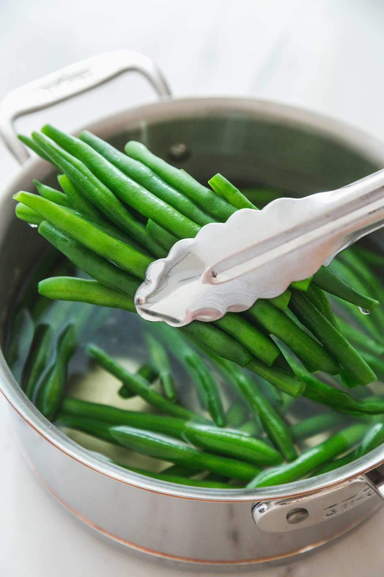 Taking blanched green beans with tongs from a saucepan