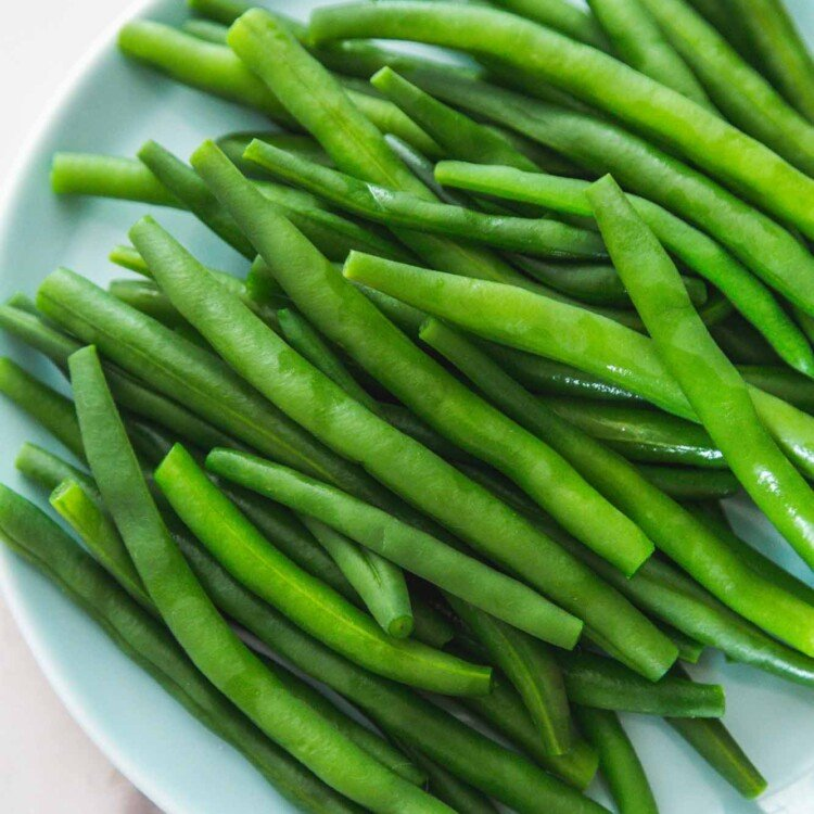 Overhead shot of blanched green beans on a blue side plate