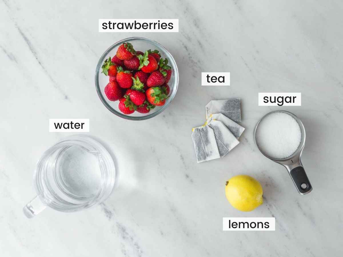 Ingredients needed to make iced strawberry tea including fresh strawberries, tea bags, water, lemon, and sugar.
