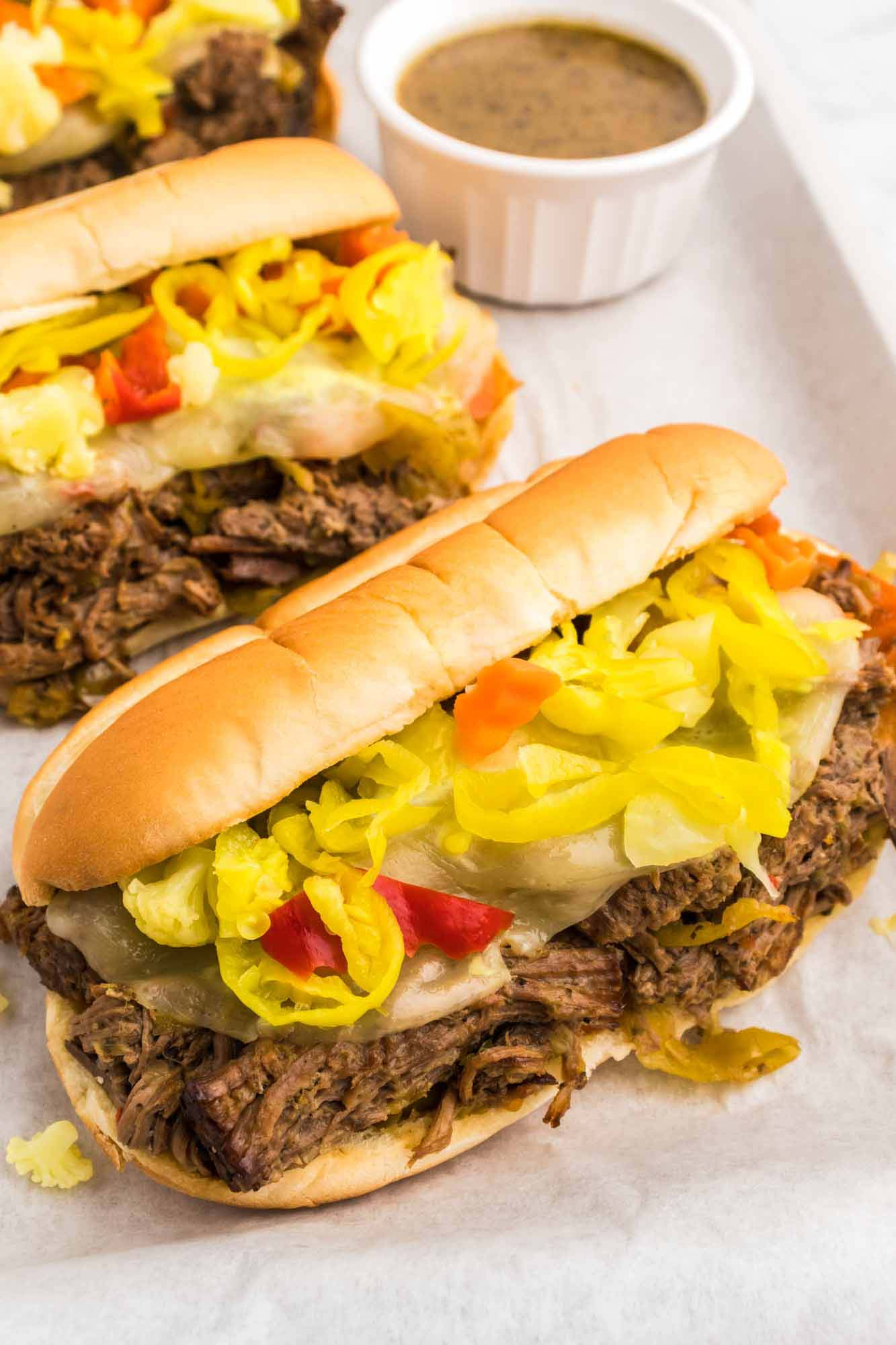 3 Italian beef sandwiches placed on parchment paper, and a little jus in a bowl for dipping.
