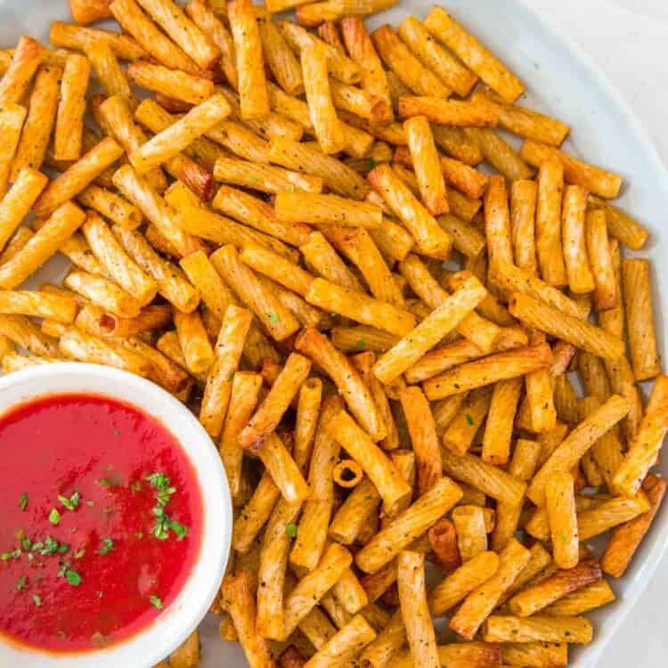 Pasta chips served on a large plate, with a tomato dip on the side.