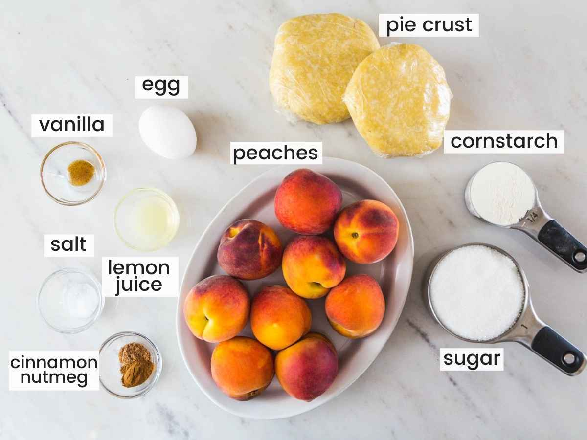 Ingredients needed for peach pie including fresh peaches, pie crust, egg, vanilla, lemon juice, cornstarch, flour, and spices.