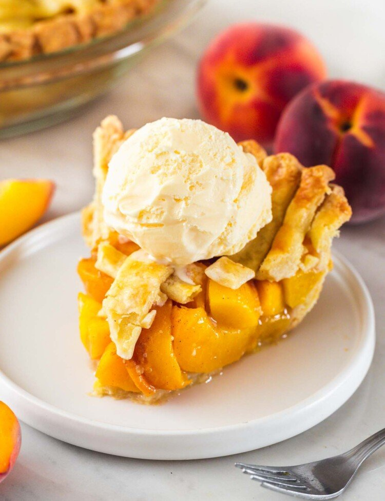 Slice of peach pie on a small white plate with a scoop of ice cream