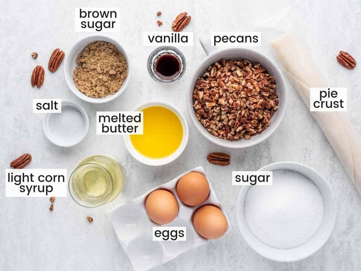 Ingredients needed to make pecan pie including pecans, pie crust, butter, eggs, sugar, salt, and vanilla.