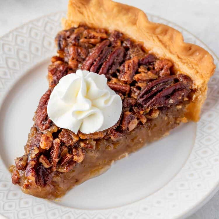 A slice of Pecan pie served on a white plate and topped with whipped cream.