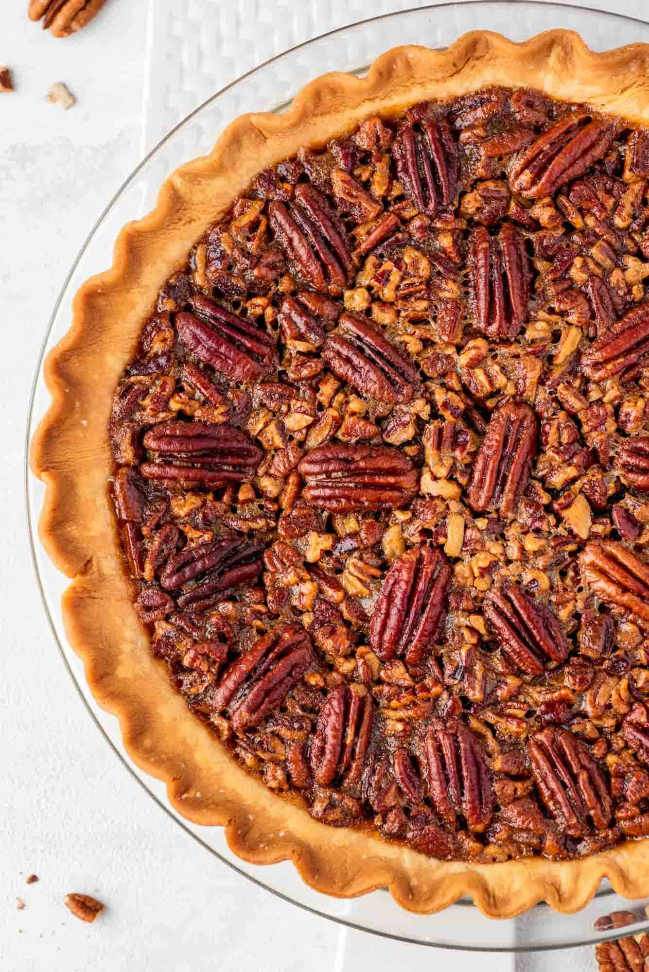 Overhead shot of a whole pecan pie in a glass pie dish