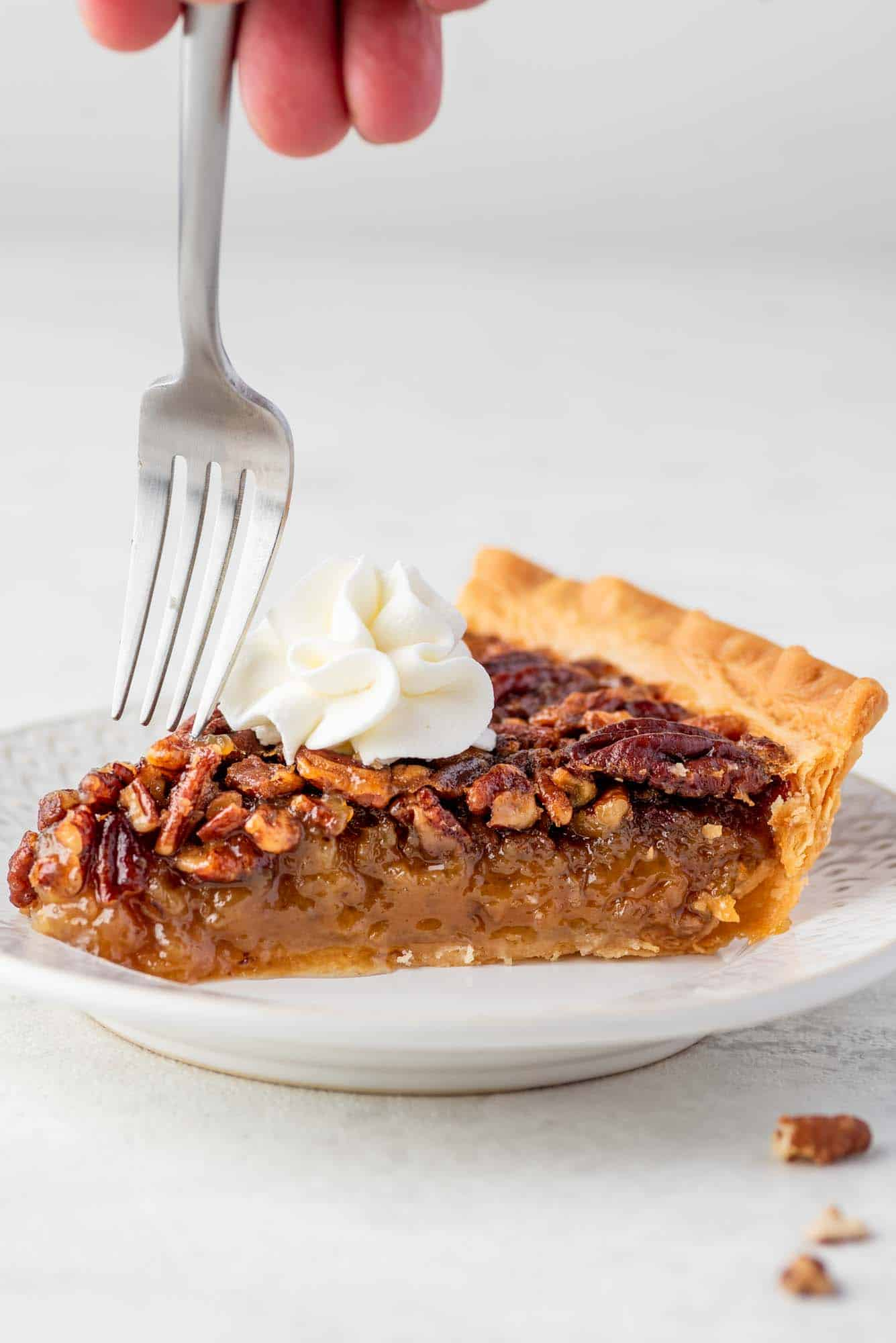 Taking a bite of pecan pie with a fork
