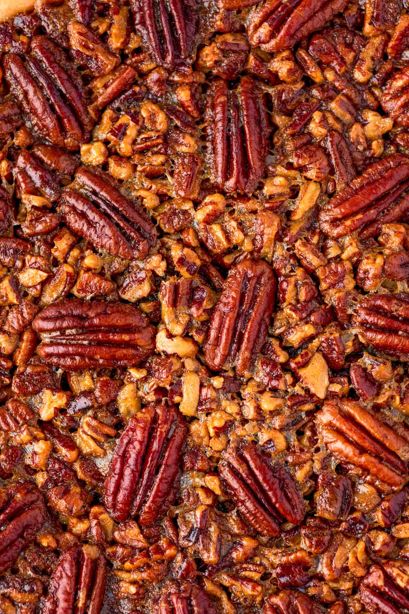 Close up shot of the top of the pecan pie with pecans that are arranged into a pretty pattern.