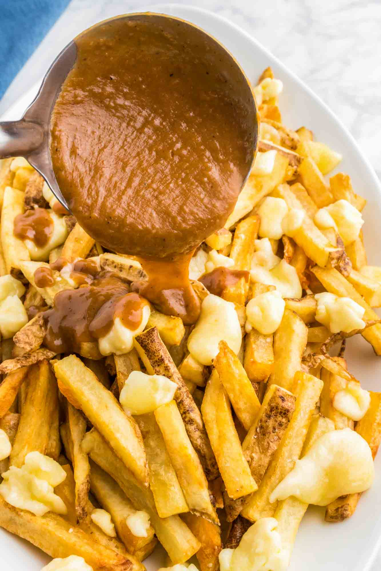 Pouting brown gravy over poutine fries and cheese curds