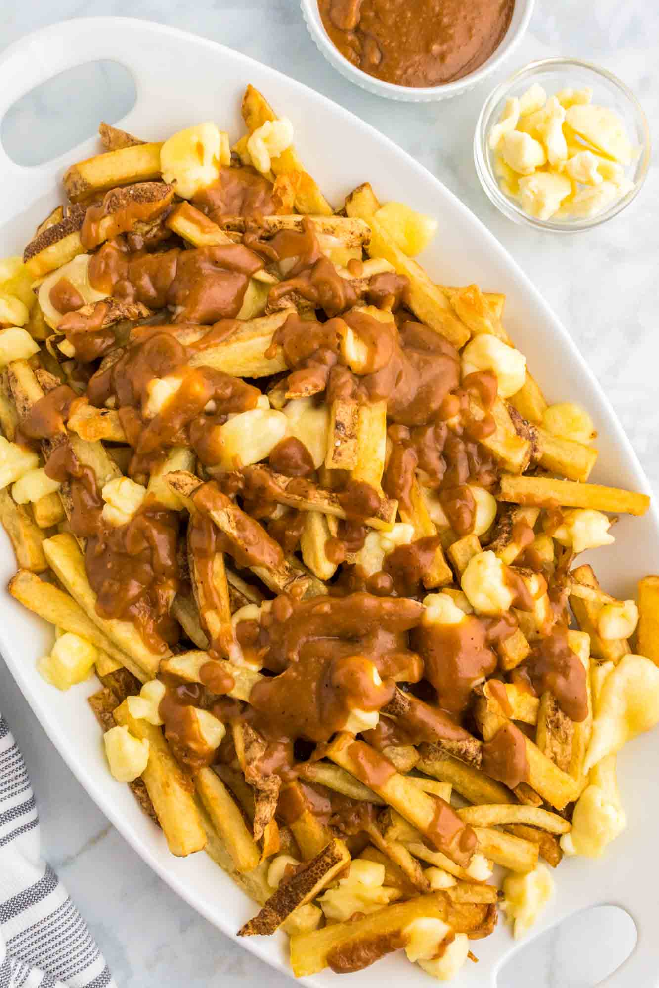 Poutine served on a large platter, with cheese curds and extra gravy on the side.
