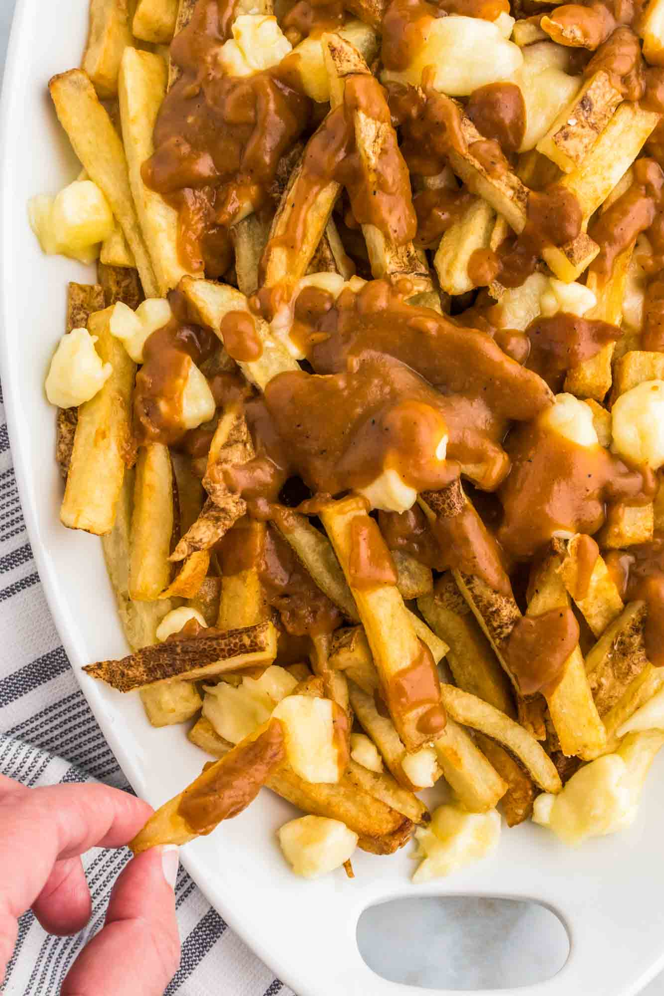 Taking a poutine fry from a platter