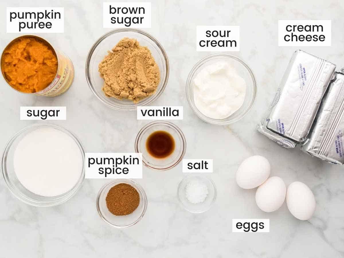 Ingredients needed to make pumpkin cheesecake filling including pumpkin puree, sugars, cream cheese, sour cream, pumpkin spice, eggs, vanilla, and salt.