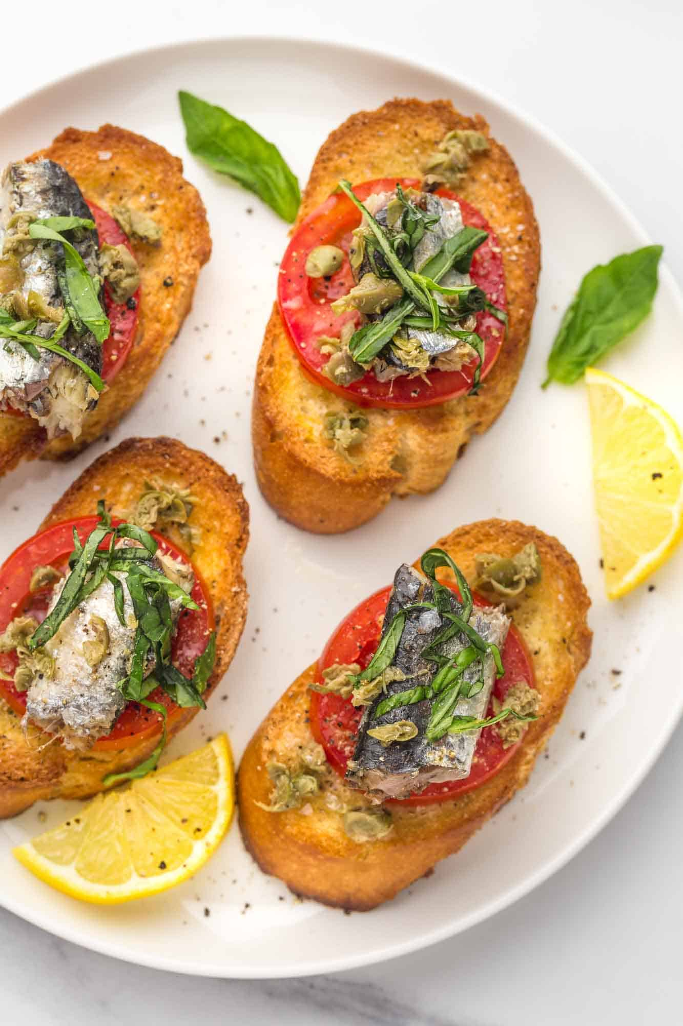 Four sardine toasts on a white plate with fresh basil leaves and lemon slices