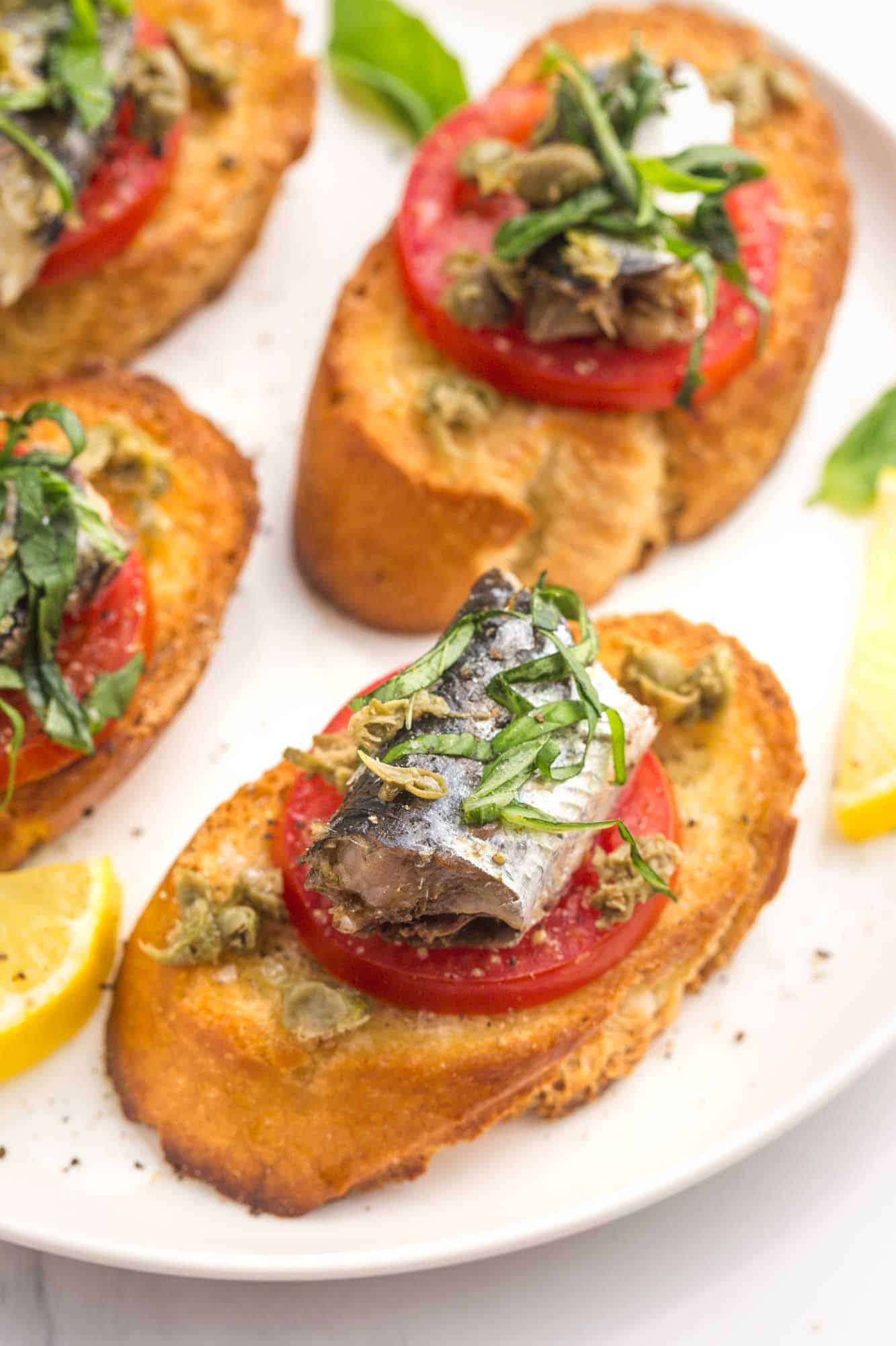 Sardines on Toast with tomato slices, capers, and basil.