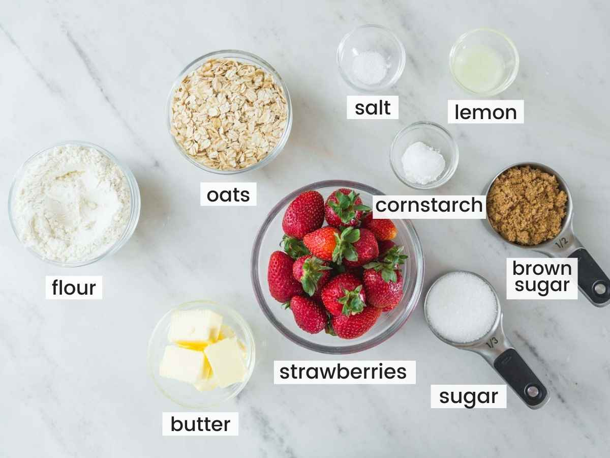 Ingredients needed to make strawberry oatmeal bars including strawberries, oats, flour, butter, lemon juice, sugars, cornstarch, and salt.