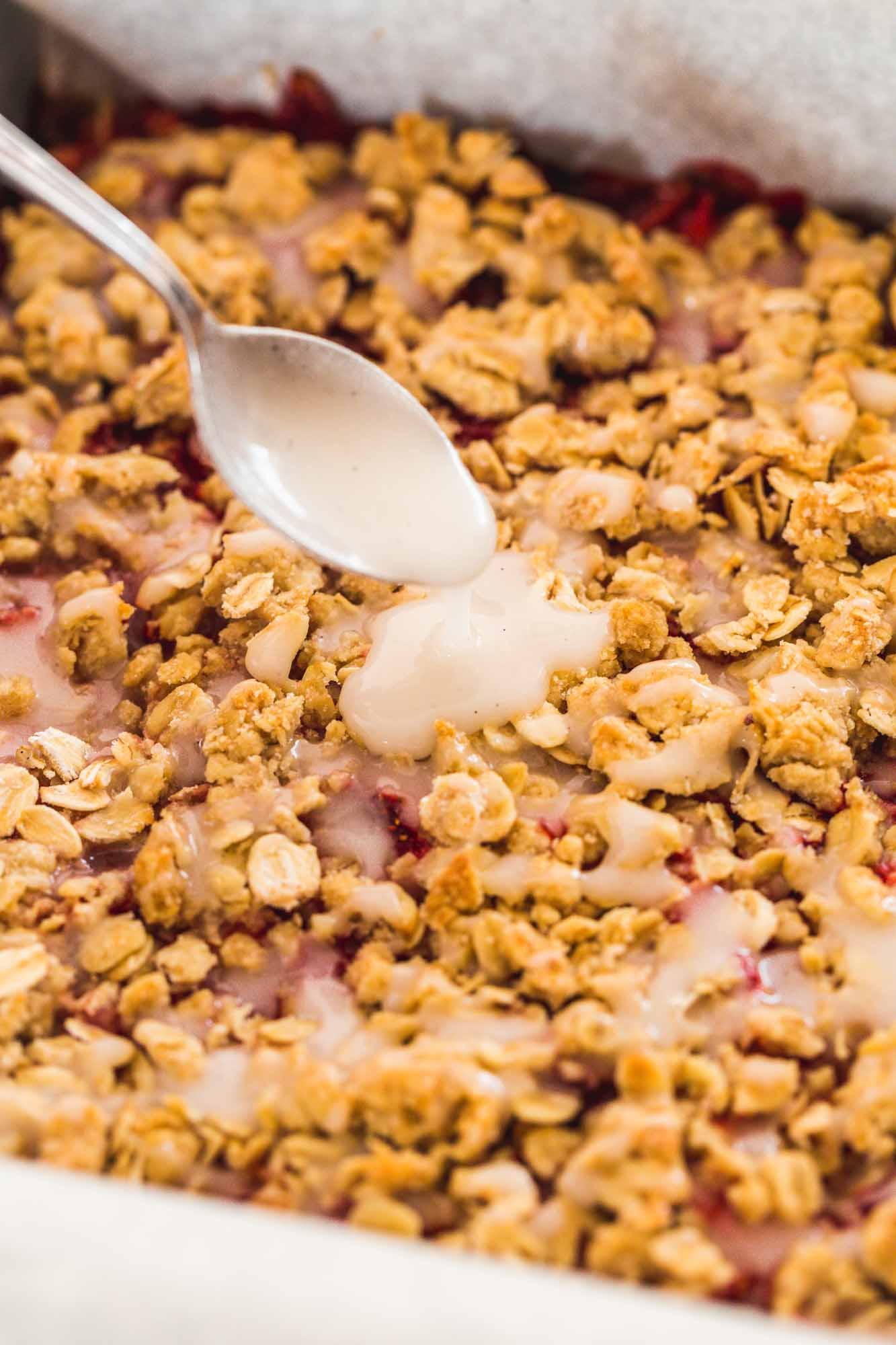 Drizzling the simple sugar drizzle over baked crumb bars