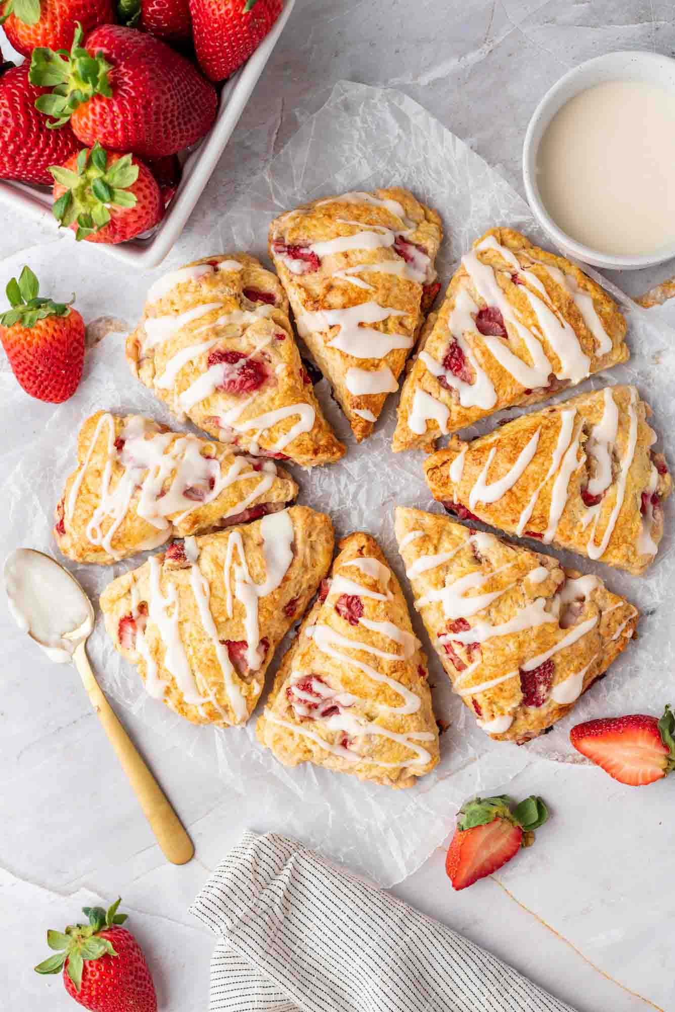 Overhead shot of eight strawberry scones with drizzle, and fresh strawberries on the side