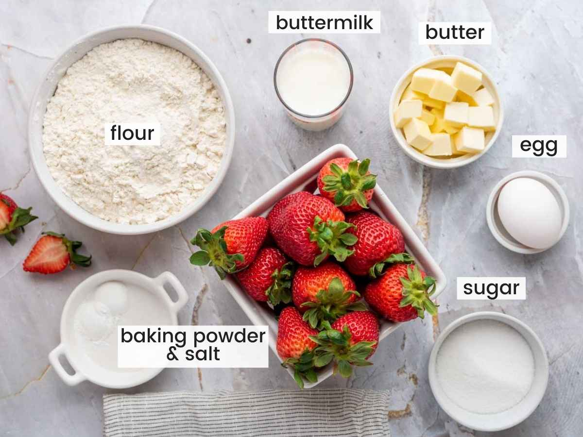 Ingredients needed to make strawberry scones including fresh strawberries, flour, cubed butter, buttermilk, sugar, egg, baking powder and salt.