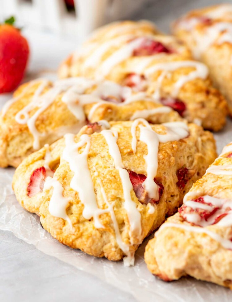 Straberry scones with white vanilla drizzle, and fresh strawberry in the background
