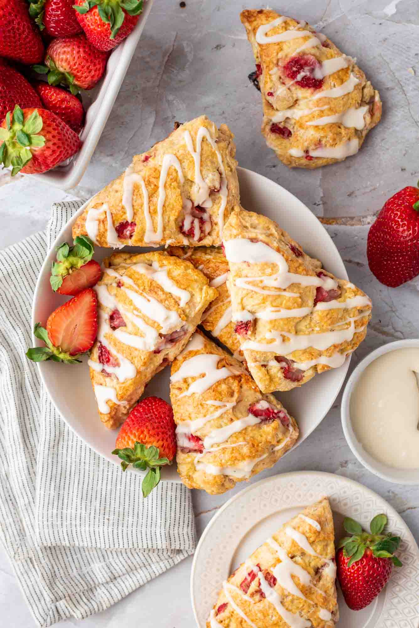 Strawberry Scones on a plate, and fresh strawberries scattered around them