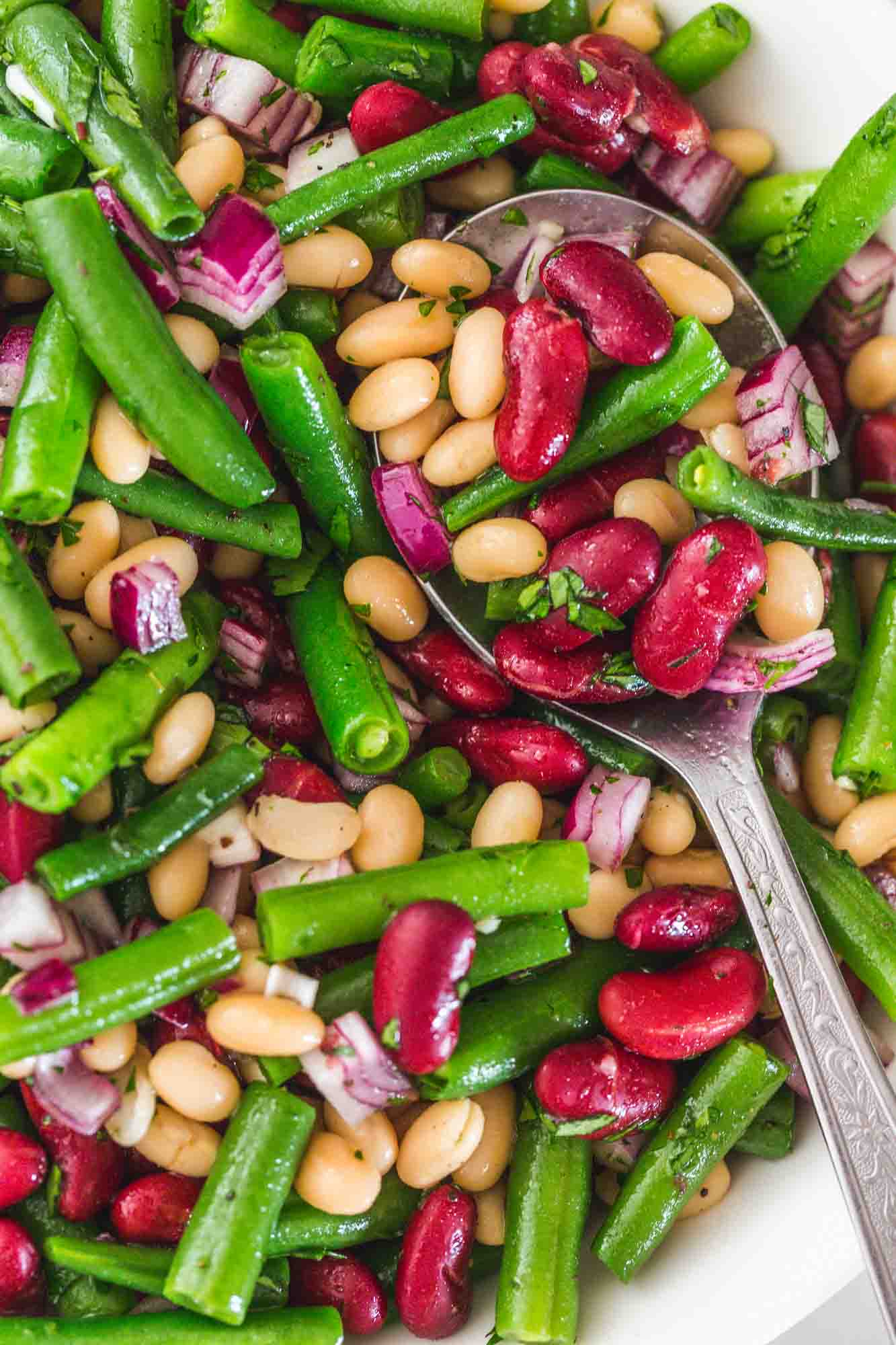 Close up shot of the three bean salad in a bowl with a serving spoon