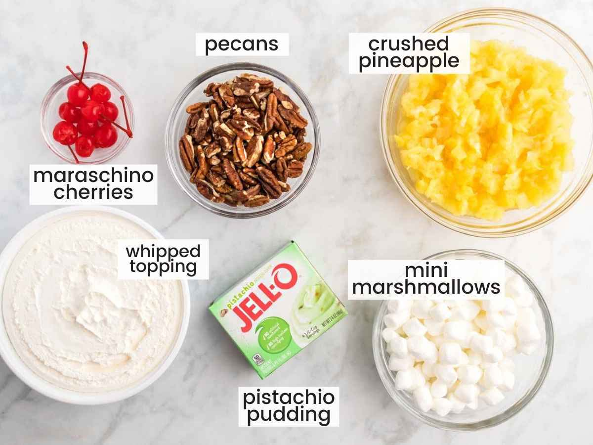 Ingredients needed to make watergate salad including pistachio pudding, crushed pineapplee, pecans, cherries, and marshmallows.