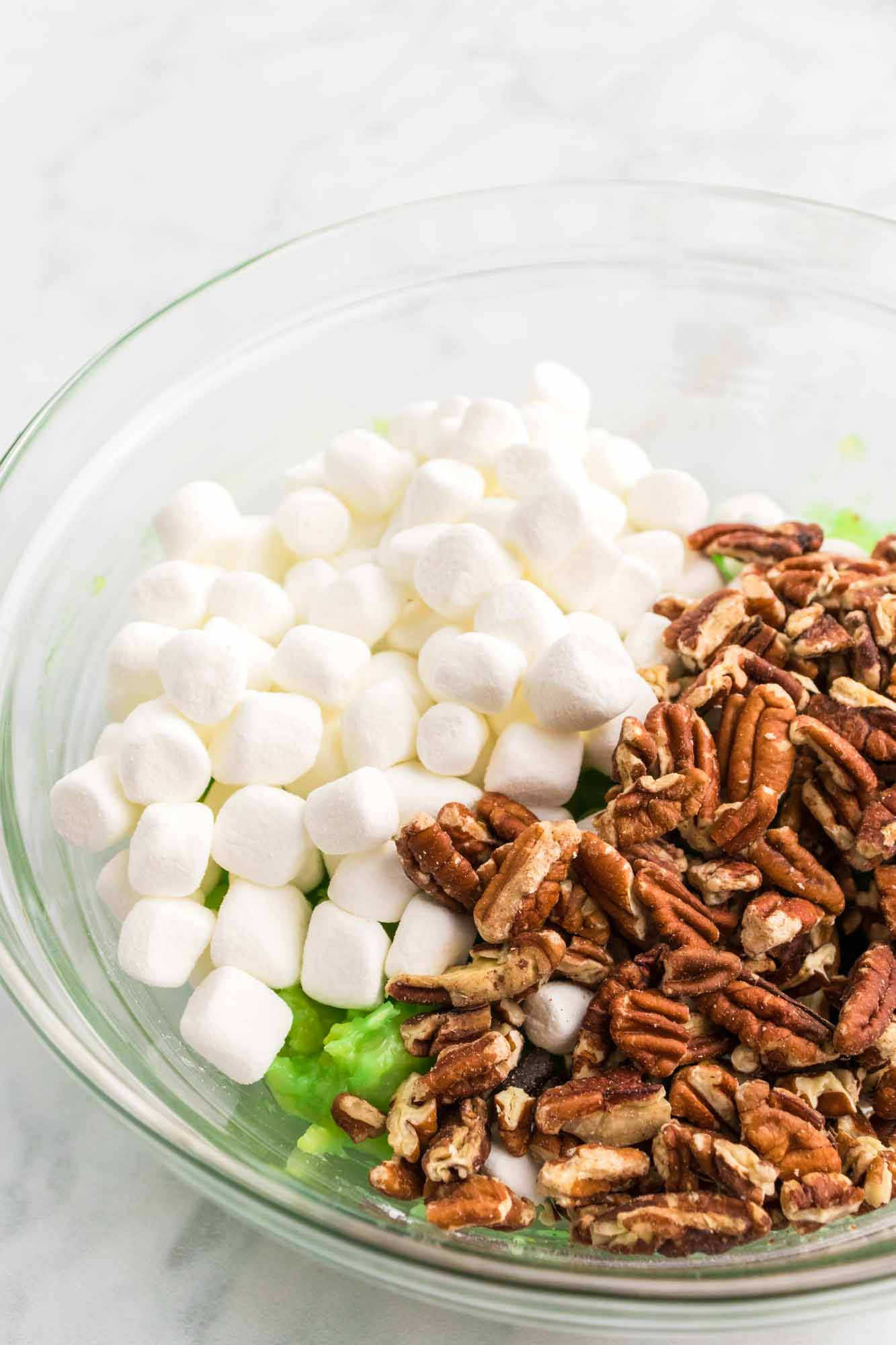 Pistachio pudding, pecans, and marshmallows in a glass bowl.