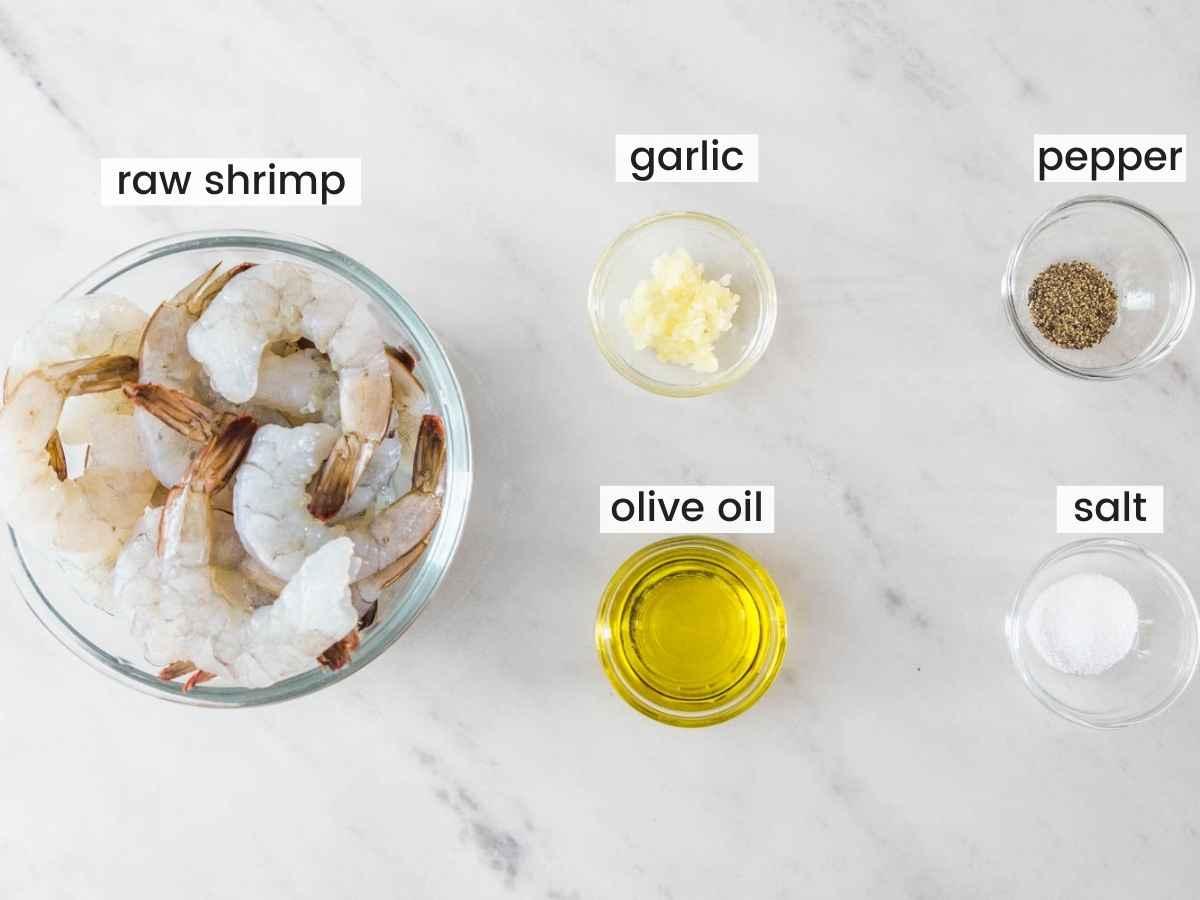 Ingredients needed to air fry shrimp including shrimp, olive oil, garlic, salt, and pepper.