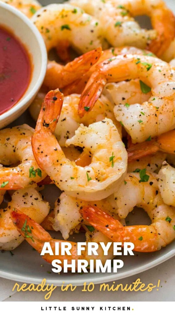 Perfectly cooked and seasoned shrimp on a plate, served with a tomato based sauce on the side
