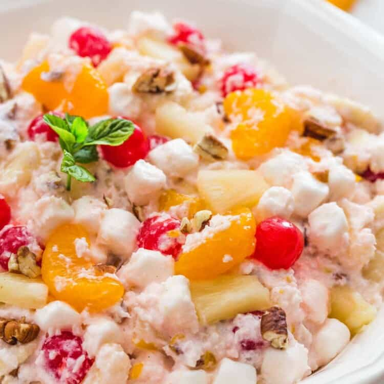 Large white plate with creamy ambrosia salad, and garnishes like fresh mint and chopped pecans