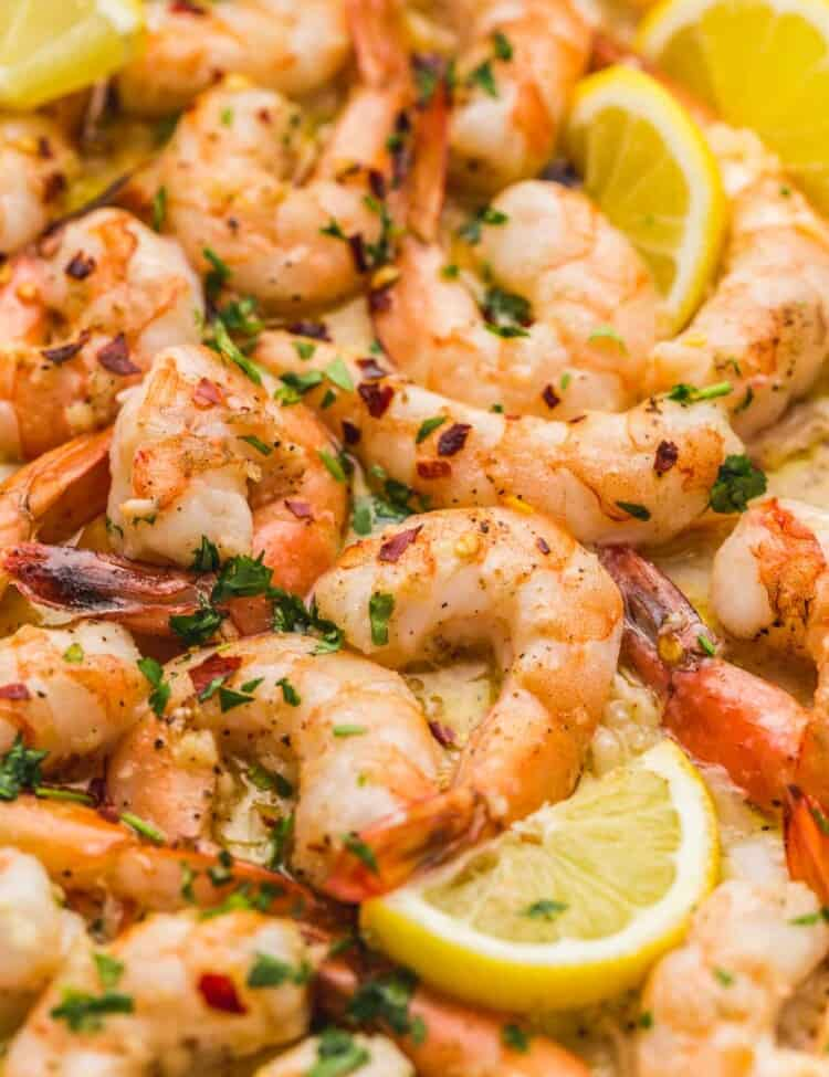Close up shot of baked shrimp with lemon wedges and garnished with parsley and red pepper flakes