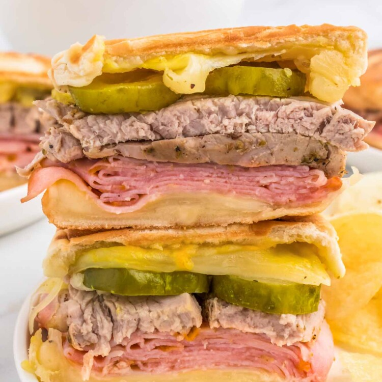 2 cuban sandwiches stacked, and served on a white plate with potato chips