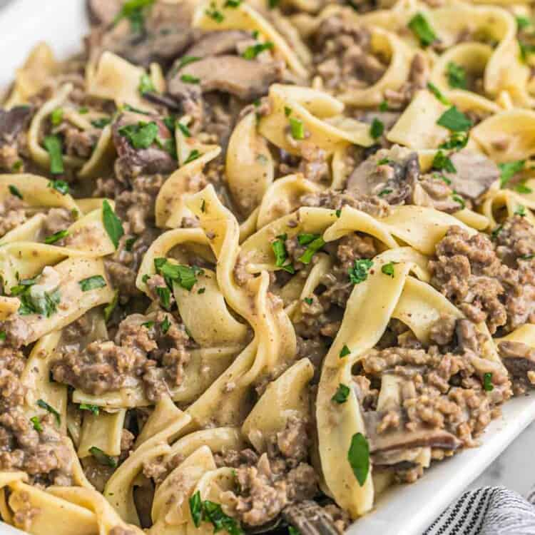 Ground beef stroganoff with egg noodles served in a white casserole dish