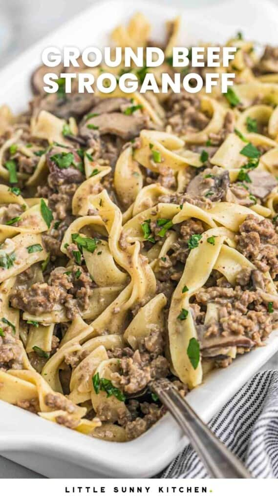 """Ground beef stroganoff served in a white casserole dish, garnished with fresh parsley leaves, and overlay text that reads """"ground beef stroganoff"""""""