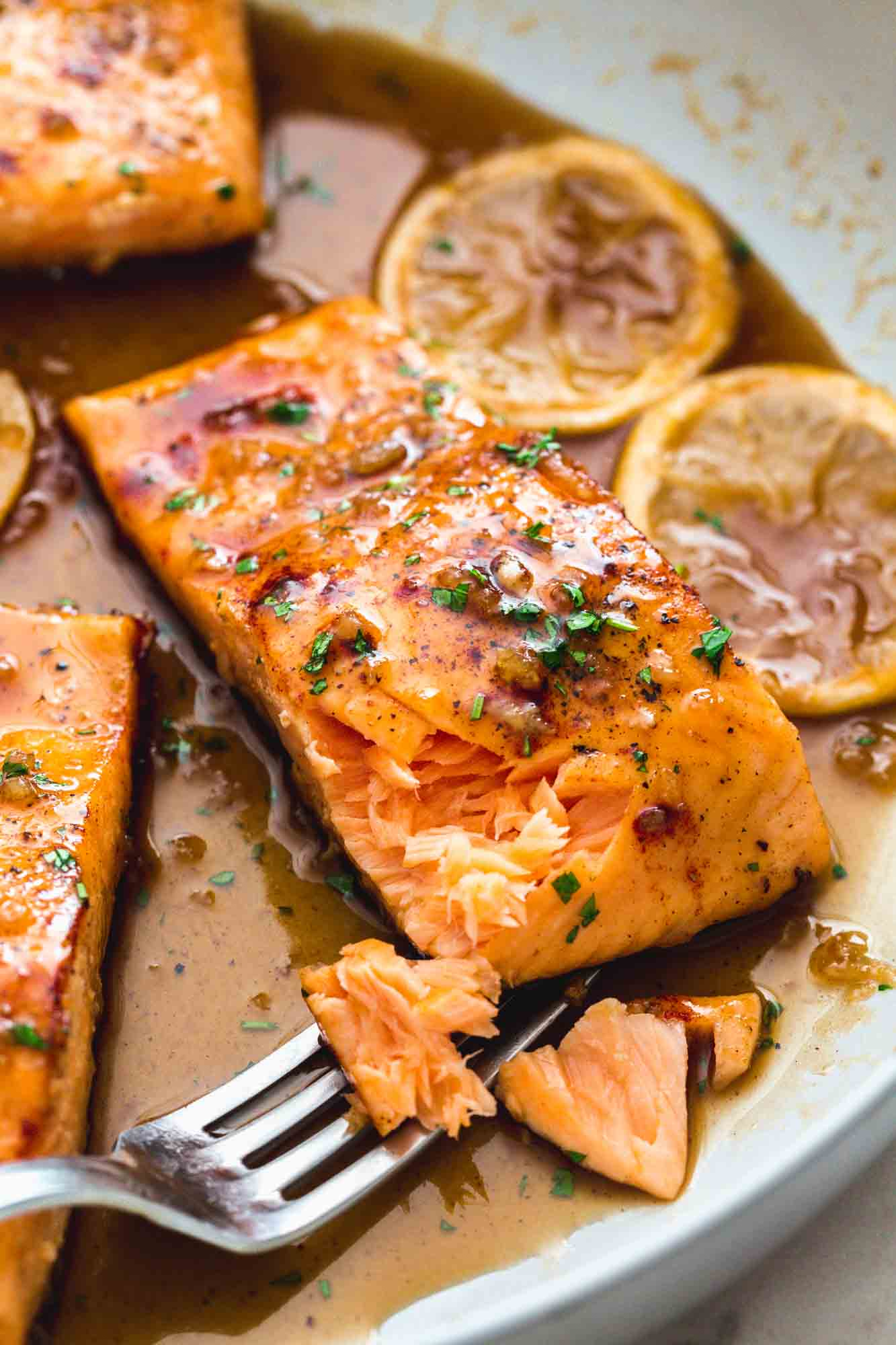 Flaked honey garlic salmon in a pan with a fork